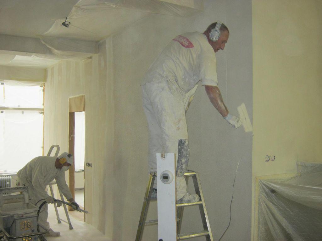 Stukadoors op de muur aan het spuiten